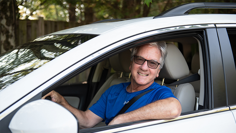 A middle-aged man is smiling as he drives a car. An easygoing guy, he's happy to provide rides to elderly in the Northern Virginia area so they can meet friends, go to the store and attend appointments. He's happy because transportation for seniors is now solved!