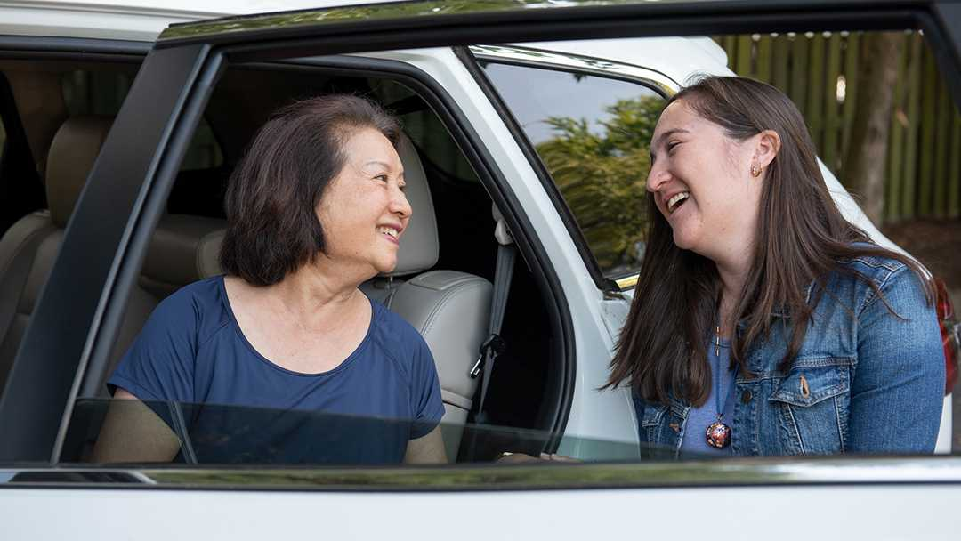 A young woman smiles at the passenger in the back seat as she exits the car. They've become friends through the NV Rides program that provides transportation services through its partner organizations. Both are happy because transportation for seniors is now solved!