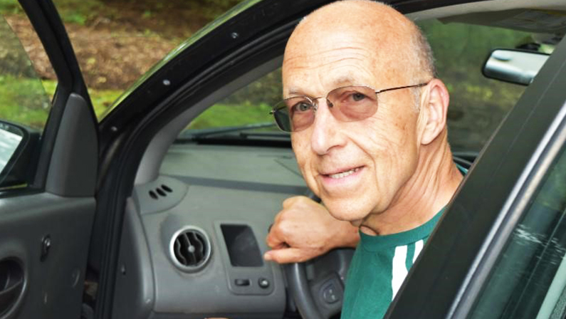Volunteer driver, Mark Turco smiles as he exits his car. He is a volunteer driver to a program that provides transportation to aging adults in the Northern Virginia area. He's happy because transportation for seniors is now solved!