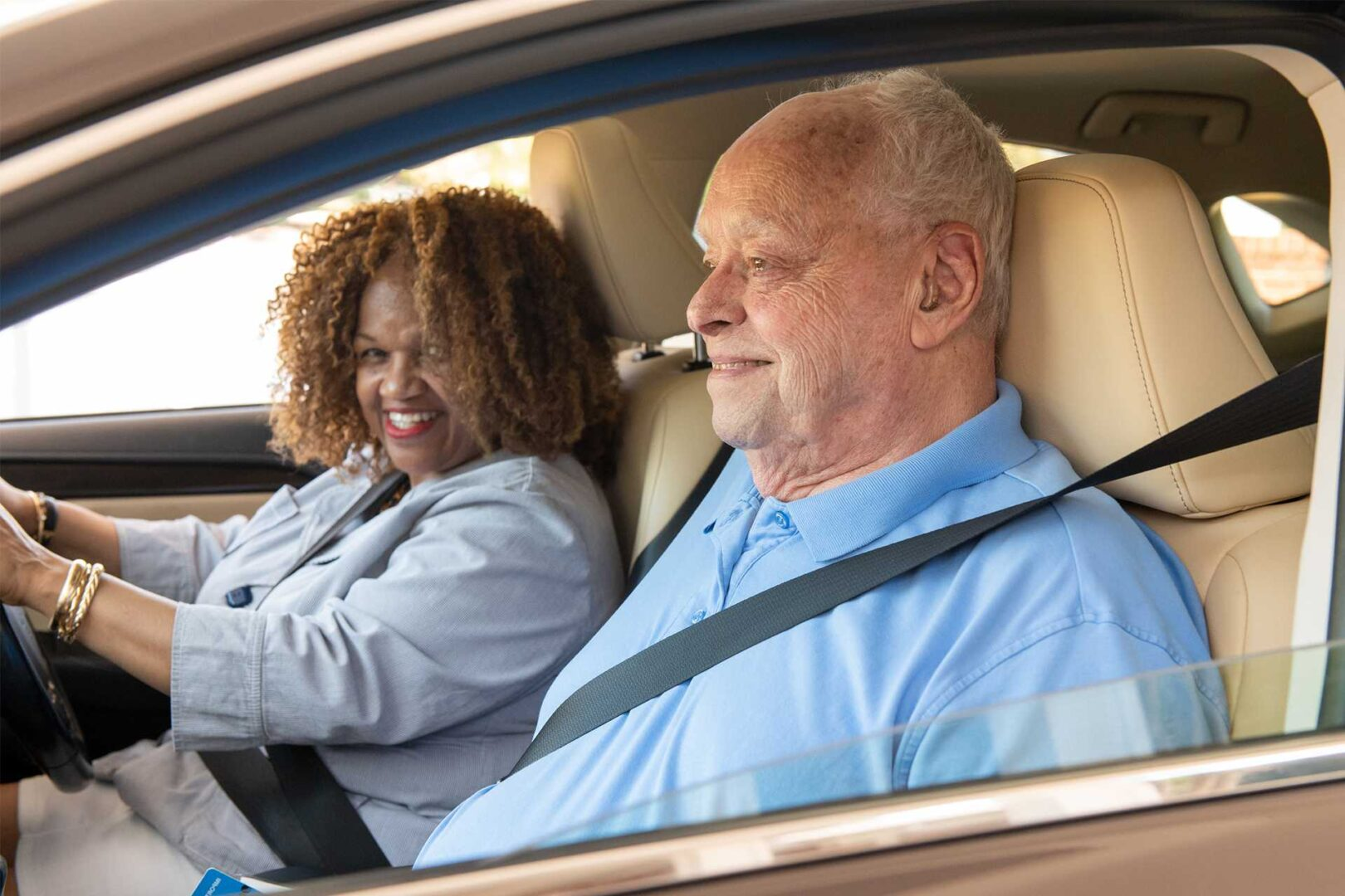 A young woman is the driver of a car with an elderly gentleman in the front passenger seat. Both are smiling because transportation for seniors is now solved!