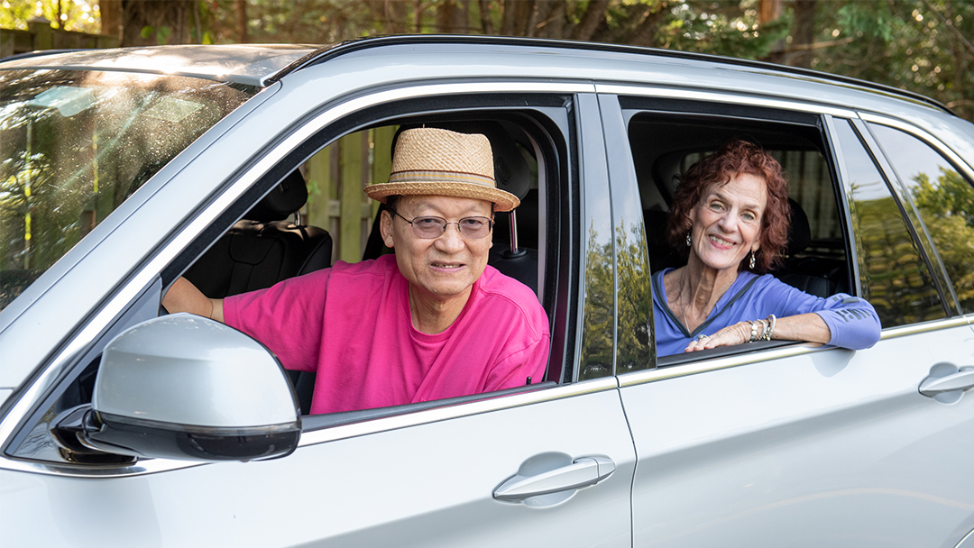 A gentleman provides a ride to an aging woman who is need of transportation to get around town. Both are smiling because transportation for seniors is now solved!
