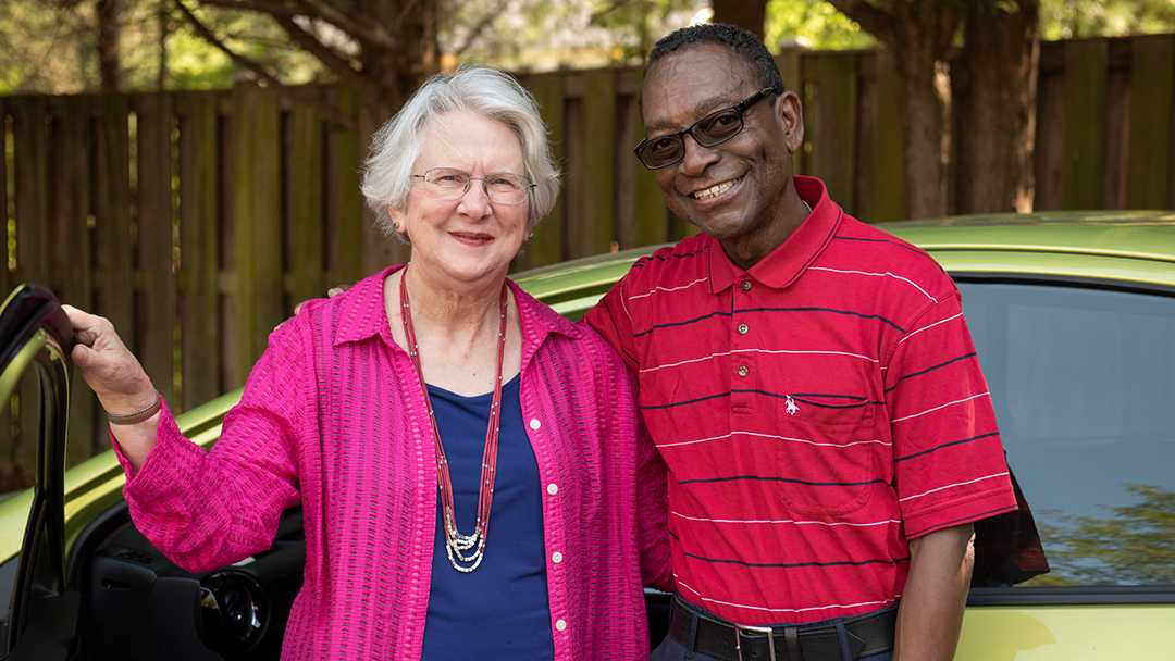 A happy man and a woman are standing at the open door of a car. They are friends who have met through the NV Rides program. Both are happy because transportation for seniors is now solved!