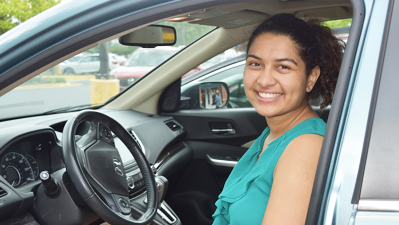 Smiling NV Rides volunteer, Rhea Sharma. She is sitting in the driver seat of a car. She's happy because transportation for seniors is now solved!