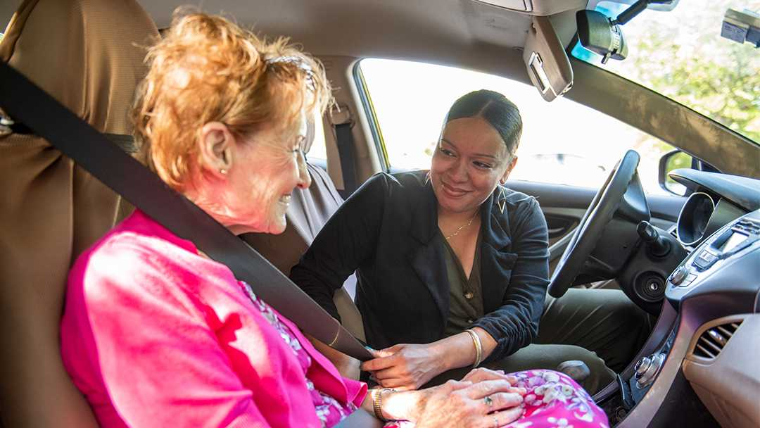 A young woman helps an elderly woman with her seat belt in the front seat of a car. They are enjoying the friendship they've developed through the NV Rides transportation partnerships. Both are happy because transportation for seniors is now solved!