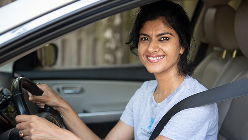 A young woman is smiling as she sits in the driver seat of a car. She provides transportation for elderly in her neighborhood through the NV Rides partners program. She is happy because transportation for seniors is now solved!