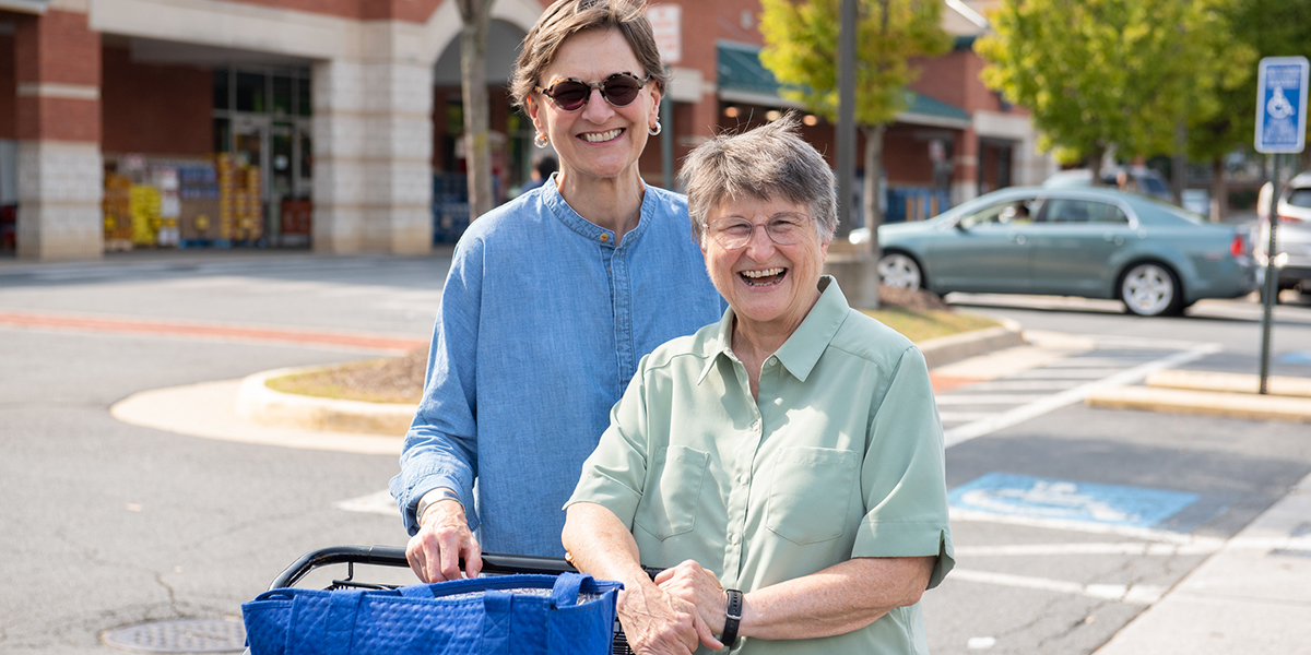 A woman helps another woman with putting groceries in the trunk of a car. They have become friends through a driving/riding partnership. Both are smiling because transportation for seniors is now solved!